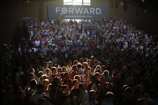 Late afternoon light streams in to illuminate part of the crowd cheering U.S. President Barack Obama during a campaign rally at the Iowa State Fairgrounds in Des Moines