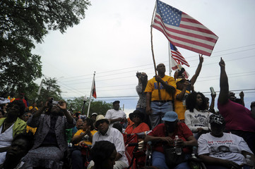 Protestors watch an NAACP march and rally in front of the Sanford Police Department for Trayvon Martin in Sanford, Florida