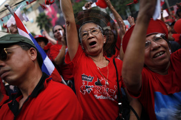 """Thai anti-government """"red shirt"""" protesters react as their leader addresses them at Bangkok's shopping district"""