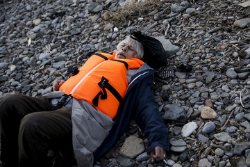 A migrant collapses from exhaustion, moments after arriving on a raft on the Greek island of Lesbos
