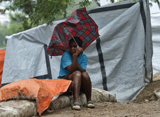 A woman uses a broken umbrella to shelter herself from the rain in Port-au-Prince