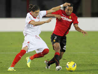 Sevilla's Caceres fights for the ball with Mallorca's Nsue during their Spanish First division soccer match in Palma de Mallorca