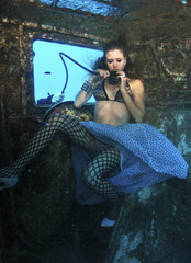 A model breathes from a scuba tank during an underwater photo shoot in the Red Sea in Eilat