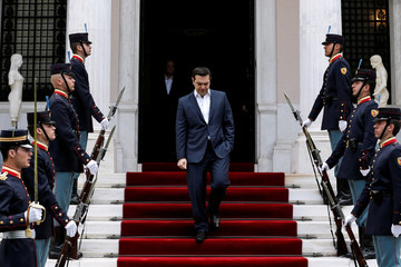 Greek PM Tsipras walks down the stairs of the Maximos Mansion next to an honorary guard as he arrives to welcome Portugal's PM Costa in Athens