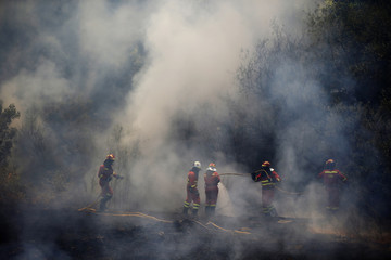 Firefighters work to control a wildfire outside Cebreros