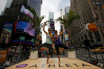 Women make a pose during an event where people practice yoga in Times Square as part of a Summer Solstice celebration on International Yoga Day in New YorK