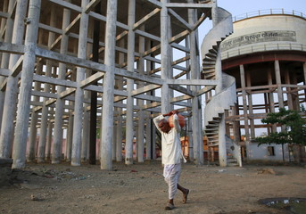 A man carrying a plastic container filled with walks past water tanks in Latur