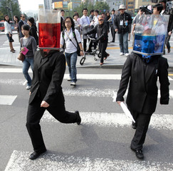 """Performers wearing transparent boxes with water cross the street at a pedestrian crossing during their street performance """"Waterheads"""" in central Seoul"""