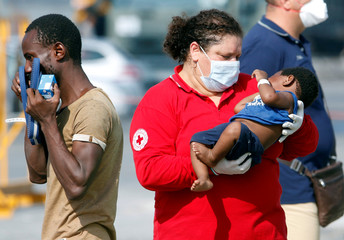 A Red Cross member carries a child as migrants disembark from the Italian Navy vessel Sfinge in the Sicilian harbour of Pozzallo