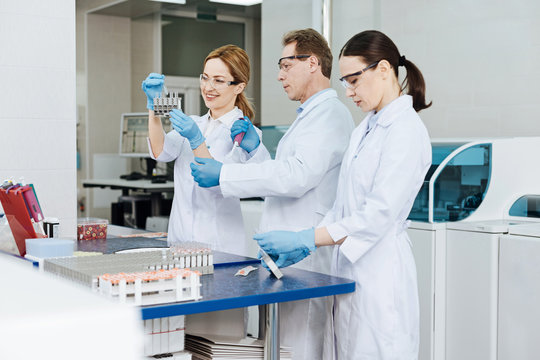 Line of three colleagues working at modern lab