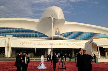 People stay in front of the terminal of the newly built airport with a portrait of Turkmen President Kurbanguly Berdymukhamedov seen in the background during its official opening in  Ashgabat, Turkmenistan