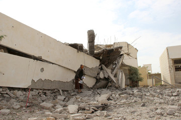 Man stands on the rubble of a school destroyed by a Saudi-led air strike in an outskirt of the northwestern city of Saada