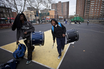 "Members of a drumline known as the ""Marching Cobras"" leave a practice at a basketball court in the Harlem neighborhood of New York"