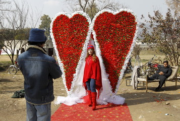 An Afghan man takes a picture of his sister in front of large heart shaped flower arrangement at a flower market on Valentine's Day in Islamabad