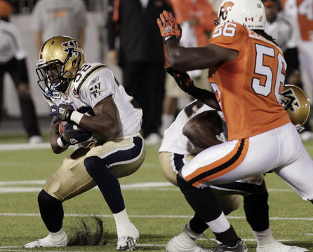 Lions Elimimian chases Blue Bombers Reid during their CFL game in Vancouver