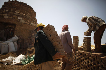 Worker carries dried mud blocks to a kiln where they are fired at a traditional brick manufacturing site in Sanaa