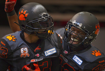 B.C Lions' Harris celebrates his touchdown against the Calgary Stampeders with Lumbala during the first half of their CFL football game in Vancouver
