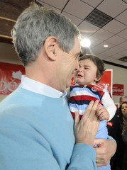 Liberal Party leader Ignatieff holds a crying baby at his campaign headquarters in Toronto