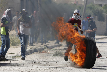 A Palestinian protester pushes a burning tyre during clashes with Israeli troops following a protest marking Nakba, near the West Bank city of Ramallah
