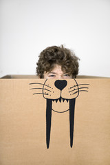 Boy inside a cardboard box painted with a saber-toothed tiger