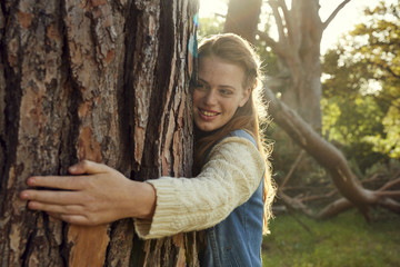 Portrait of smiling young woman hugging tree trunk at backlight