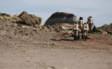 Members of Crew 125 EuroMoonMars B mission venture out in their simulated spacesuits to collect geologic samples in the Utah desert