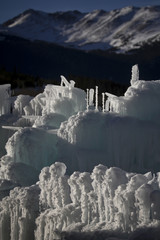Mountains are seen in the background of ice formations at the Ice Castles at Silverthorne in Colorado