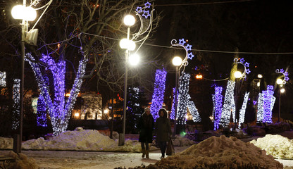 Women walk at the Lenin avenue, which is lit with festive illuminations before Orthodox Christmas, in central Volgograd