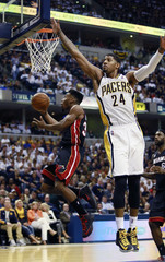 Heat's Cole goes up to the basket past Pacers' George in the second half of Game 3 of their NBA Eastern Conference final basketball playoff series in Indianapolis