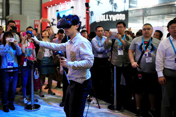 A man tests a virtual reality product, VIVE from Intel at CES Asia 2016 in Shanghai