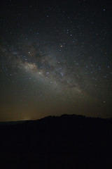 Milky Way over mountain at Phu Hin Rong Kla National Park,Phitsanulok Thailand, Long exposure photograph.with grain