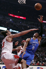 Thunder point guard Westbrook is guarded by Bulls center Noah during the first half of their NBA basketball game in Chicago