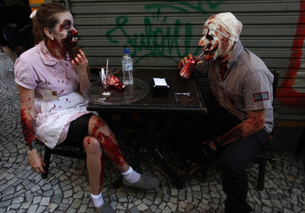 A couple, made up to look like zombies, chats as they take part in a zombie parade in Sao Paulo