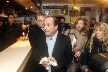 Hollande, Socialist Party candidate for the 2012 French presidential election, and his companion Trierweiler, a French journalist, visit a bar in Tulle