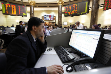 A trader works at the Egyptian Stock Exchange after its reopening, in Cairo