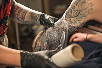 Woman enveloping tattoo arm of client