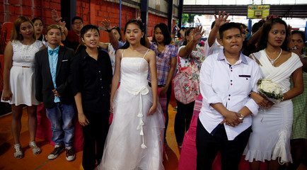 Relatives and friends place their hands near the heads of couples during a same sex wedding ceremony officiated by Reverend CJ Agbayani of the Christian Church Inc in Quezon city, Metro Manila