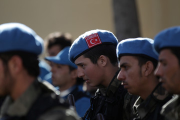 """A member of the Free police, wearing a Turkish flag on his hat, attends a ceremony celebrating the inauguration of the """"Free Police"""" in the Syrian border town of Jarablus"""