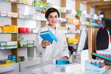 Female pharmacist offering help in choosing at counter in pharmacy