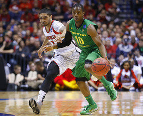 Oregon Ducks Loyd is chased by Louisville Cardinals Siva during their Midwest Regional NCAA men's basketball game in Indianapolis