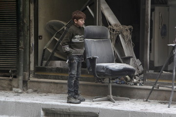 A boy inspects damage after airstrikes by pro-Syrian government forces in the rebel held Al-Shaar neighbourhood of Aleppo, Syria