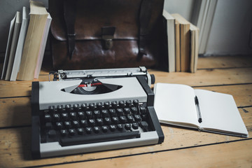 A vintage gray typewriter on a wooden floor. Notepad, pen, books and leather briefcase on the wooden floor