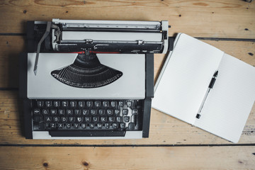 A vintage gray typewriter on a wooden floor. Notepad and pen on the wooden floor