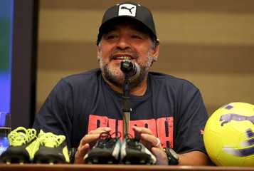 "Argentina's former soccer player Diego Maradona smiles during a news conference for a ""pro-peace"" soccer match in Bogota"