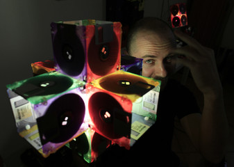 Romanian actor Teglas shows a lamp he made from recycled floppy disks in Bucharest
