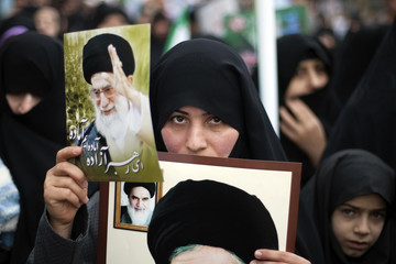 Woman holds pictures of Iran's Supreme Leader Khamenei and late Leader Khomeini during rally to mark anniversary of Islamic Revolution in Qom