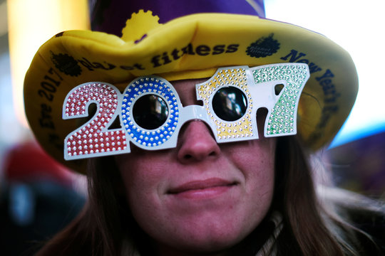 """A reveler poses for a photo as she wears glasses that read """"2017"""" in during New Year's Eve festivities in the Times Square area of New York"""