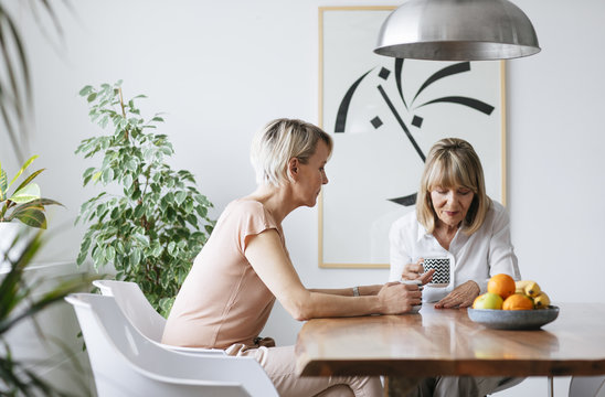 Pretty senior Caucasian woman drinking coffee in dining room with her daughter and talking.