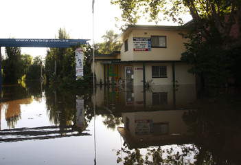 A house is reflected in flood waters near the caravan park in Wagga Wagga