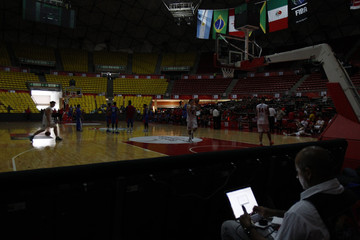Players of Paraguay and Dominican Republic warm up while they wait for the power returns after a blackout during their FIBA Americas Championship basketball game in Caracas